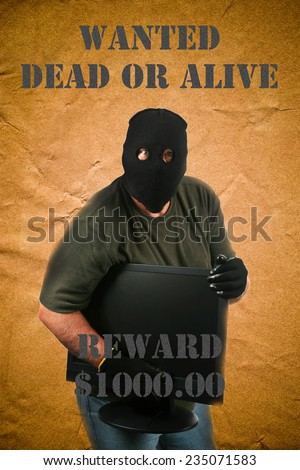 A genuine Bad Guy aka Burglar holds a stolen computer monitor while posing on a Wanted Dead or Alive poster.  - stock photo