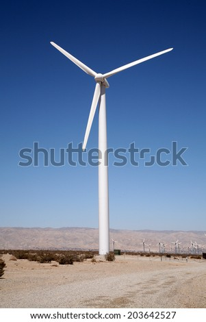 A Genuine Earth Saving Electrical Generating Wind Turbine sits in the Hot Dry Desert of Palm Springs California, making Free Green Electricity with the power of the wind for the greater good of man - stock photo