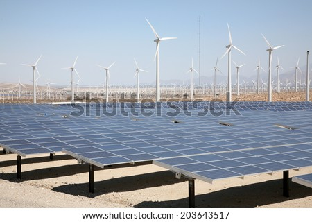 A Genuine Energy Farm in the Hot Arid Desert of Palm Springs California features Solar Panels and Wind Turbines to Harness the Power of Nature to generate free green energy to sell to the masses - stock photo