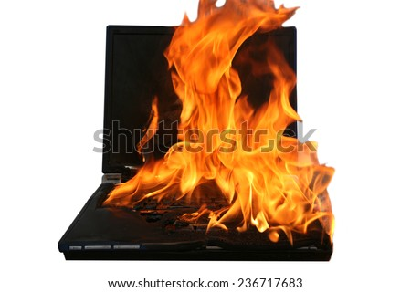 a Genuine Laptop Computer on fire. Isolated on white with room for your text. Represents Hot Love, Burning up the Internet, Setting the World on Fire, Computer Damage, Insurance claims, Hell Fire etc. - stock photo