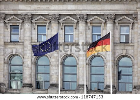 A German and European Union flag in front of the German Bundestag in Berlin. - stock photo