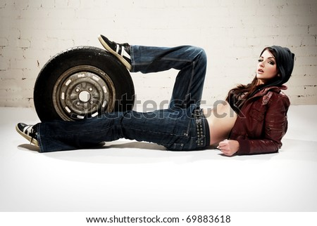 A ghetto styled girl posing in front of brick wall with a wheel - stock photo