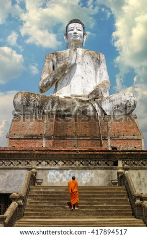 A giant Buddhist statue and a monk in Cambodia. An unidentifiable lone Buddhist Monk walks up the stairs towards the big Buddha. You can easily isolate the sky and put your own in. - stock photo