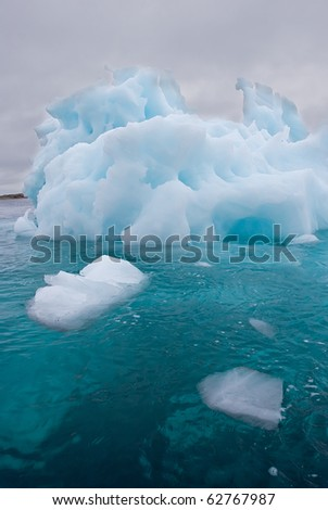 a giant iceberg floating under a stormy sky - stock photo