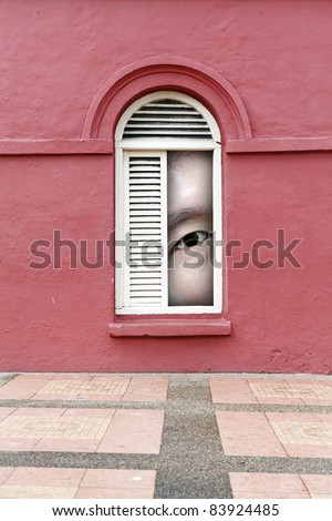 A giant man's eye peeping through a vintage timber louver window on a grungy red mason wall. - stock photo