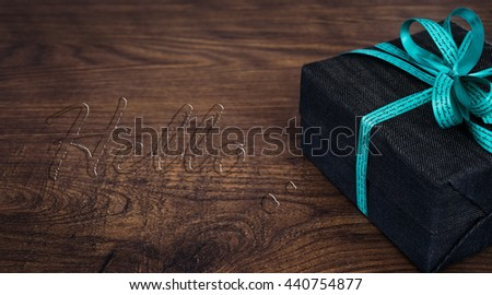 A gift box on wooden board with Hello water drop text. - stock photo