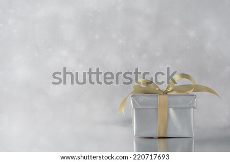 A gift box with closed lid, wrapped in metallic silver paper and tied to a bow with gold satin ribbon.  Sparkling, star lit bokeh background. - stock photo