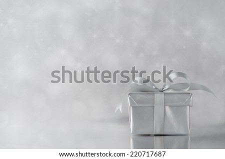 A gift box with closed lid, wrapped in metallic silver paper and tied to a bow with satin ribbon.  Sparkling, star lit bokeh background. - stock photo