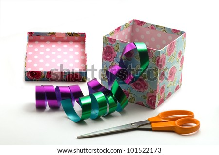A gift box with green and pink floral design and scissors - stock photo