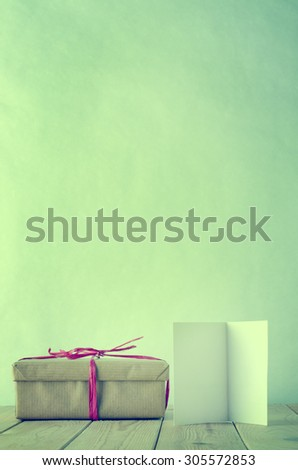 A gift box wrapped in brown paper and tied with pink raffia bow on a wooden table.  An opened, blank  greeting card faces front.  Cross processed to give a retro or vintage style. - stock photo
