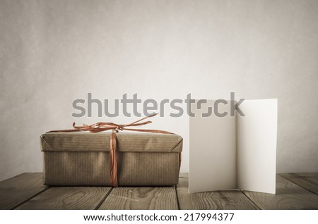 A gift box wrapped in brown paper and tied with raffia , next to an open card left blank for copy space, on an old, weathered and scratched planked table.  Low saturation for vintage effects. - stock photo