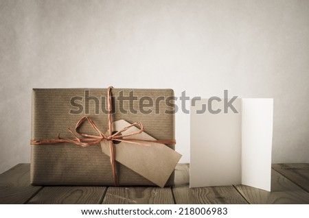 A gift box wrapped in brown paper and tied with raffia with blank label facing front. Next to a blank  open card on an old, weathered and scratched planked table.  Earthy colours. Vintage style. - stock photo