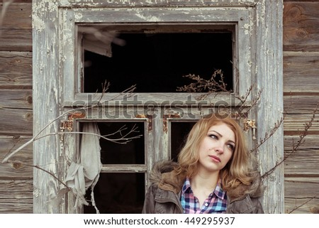 a girl, a woman is destroyed in a house fire near the broken window - stock photo