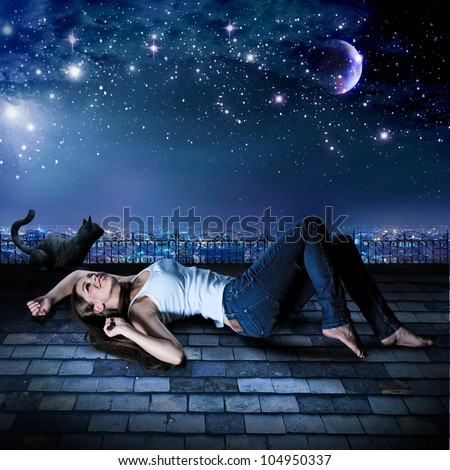 a girl and a cat are lying on a rooftop under the starry sky - stock photo