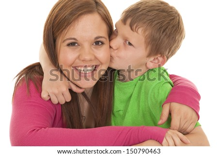 A girl and a young boy he is kissing her on the cheek. - stock photo