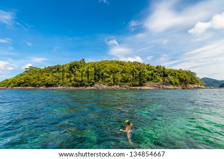 a girl and an island with beautiful sea and sky in thailand. nice place for snorkel-ling. Lipe island - stock photo