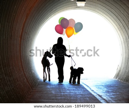 a girl at the end of a tunnel holding balloons and two dogs - stock photo