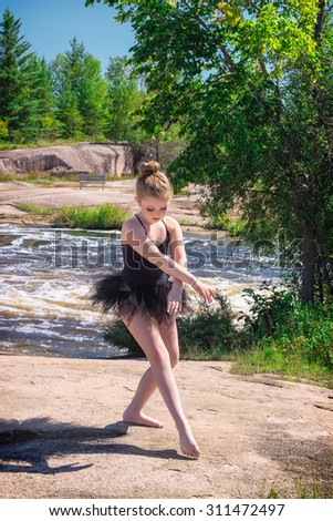 A Girl Ballerina Poses Outside by Rushing River in Green Forest - stock photo
