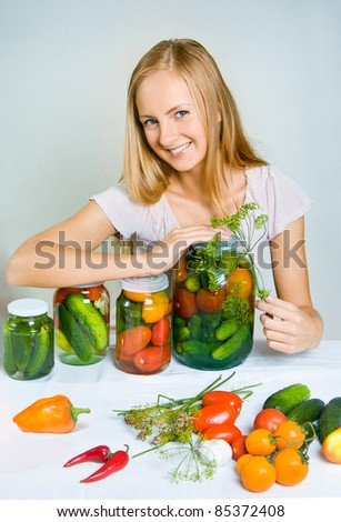 A girl can the vegetables at home - stock photo