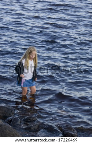 A girl concentrating on not slipping while wading. - stock photo