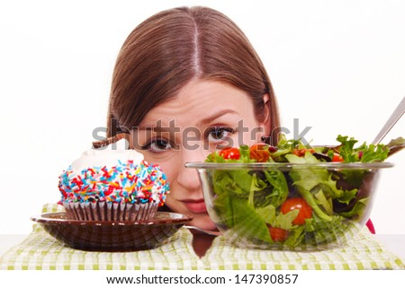 A girl deciding between cake or salad - stock photo
