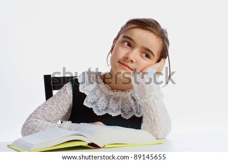 A girl dreaming above a book - stock photo