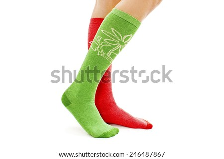 A girl dressing green-red socks. Isolated on white background  - stock photo