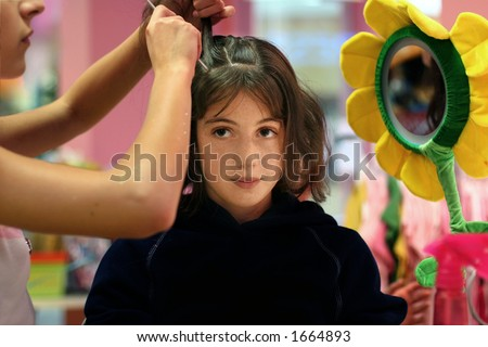 A girl getting her hair done - stock photo