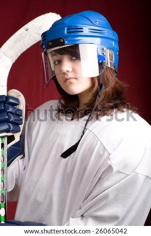 a girl hockey player in uniform posing with helmets off in front of red - stock photo