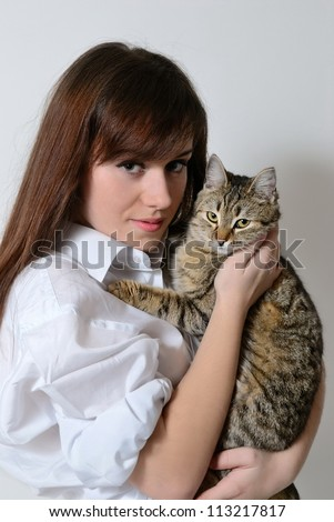 A girl holding a cat in her arms - stock photo