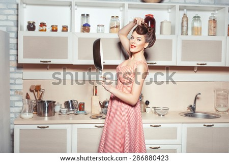 A girl holding a frying pan in front. She stands in the kitchen. Old-fashioned style. - stock photo