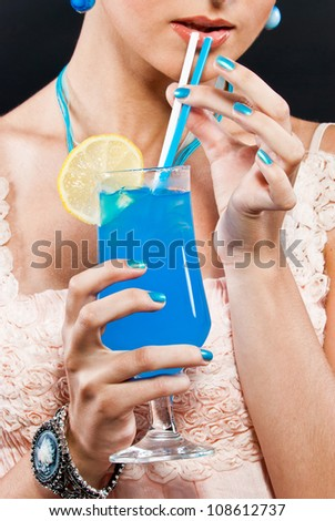 A girl holding a glass with a blue alcoholic beverage - stock photo