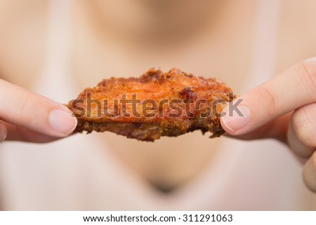 A girl holding and eatting fried chicken  - stock photo