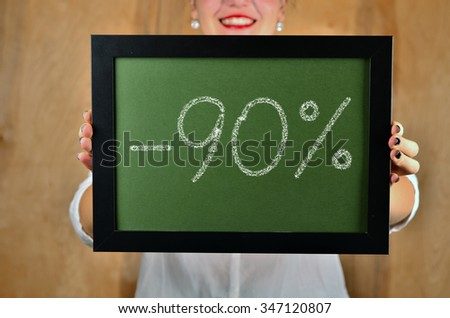 a girl holds a sign saying sale - 90 percent - stock photo
