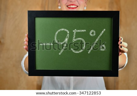 a girl holds a sign saying sale - 95 percent - stock photo