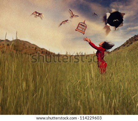 a girl in a field tossing a birdcage in the air - stock photo