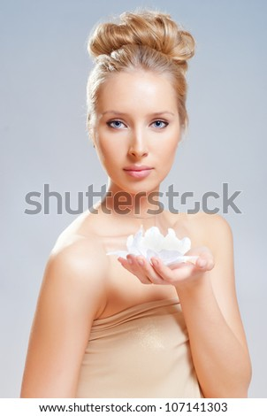 A girl in a gold dress holding a flower in her hand. - stock photo