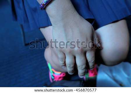 A girl in a short skirt put a hand on her knee - stock photo