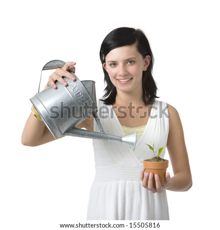 A girl in a white dress waters a plant in her hand - stock photo