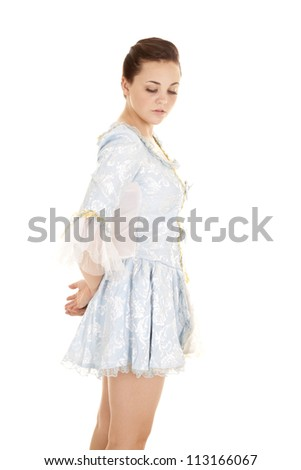 a girl in her blue dress looking down with  a peaceful expression on her face. - stock photo