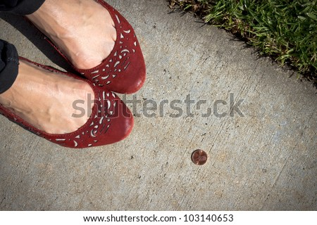 A girl in red shoes finds a penny on the sidewalk. Pick it up and you'll have good luck all day! - stock photo