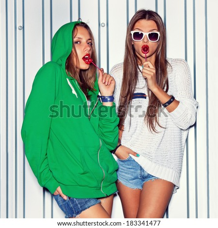 a girl in stockings is sucking a red lollipop while the other in sexy shorts is licking one  - stock photo