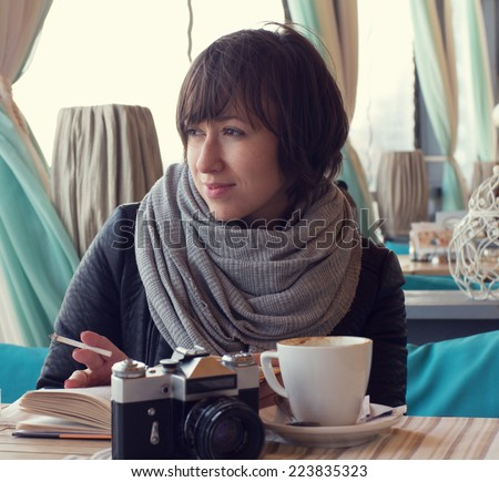 A girl in the street cafe. Retro look toned image.  - stock photo
