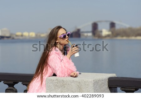 a girl  in town drinks drinks of coffee tea  teenager fashion style sits model beauty long hairs to enjoy smile bright clothes pink - stock photo
