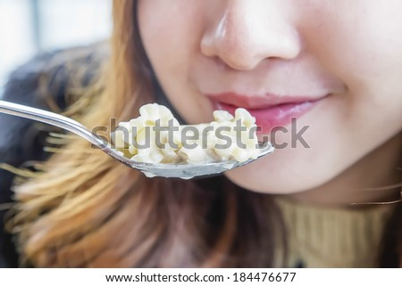 a girl is eating the pasta - stock photo
