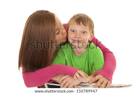 A girl is kissing a young boy on the cheek. - stock photo