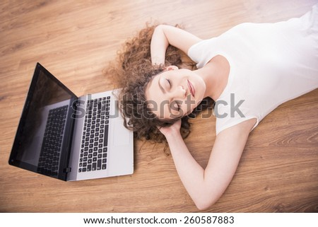 A girl is laying on the floor and is sleeping near a laptop. View from above. - stock photo