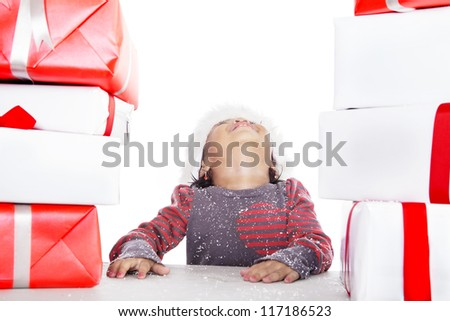 A girl is looking up with Christmas gifts beside her isolated in white - stock photo