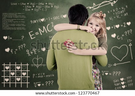 A girl is smiling because he gets a present from her boyfriend in classroom - stock photo