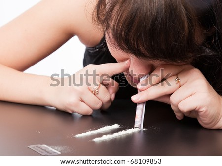 a girl is sniffing cocaine (imitation). isolated on a white background - stock photo